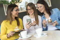 Drie vrienden genieten van koffie en cakes royalty-vrije stock afbeelding