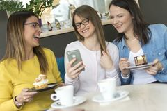 Drie vrienden genieten van koffie en cakes stock foto's