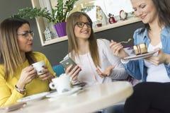 Drie vrienden genieten van koffie en cakes royalty-vrije stock foto's