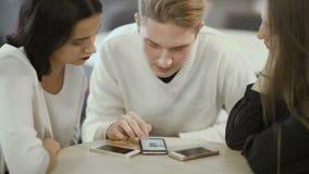 Drie vrienden kijkt op het scherm van smartphone stock videobeelden