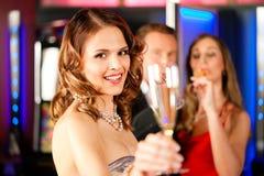 Drie vrienden met champagner in een staaf Stock Fotografie
