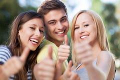 Drie vrienden met omhoog duimen Stock Fotografie