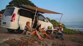 Drie vrienden op strandpicknick dichtbij kampeerautobestelwagen stock videobeelden