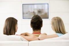 Drie vrienden in woonkamer het letten op televisie stock foto's