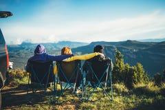 Drie vrienden zitten als het kamperen voorzitter bovenop een berg, genieten de reizigers van aard en de knuffel, toeristen onderz stock foto