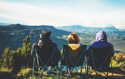 Drie vrienden zitten als het kamperen voorzitter bovenop een berg, genieten de reizigers van aard en de knuffel, toeristen onderz royalty-vrije stock afbeeldingen