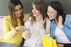 Drie vrienden zitten en gebruiken een mobiele telefoon stock afbeeldingen