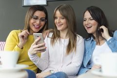 Drie vrienden zitten en gebruiken een mobiele telefoon stock foto's
