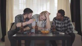Drie vrienden zitten samen in het huis en steunen en juichen omhoog ??n van de vriend toe die droevig is Ware vriendschap stock videobeelden