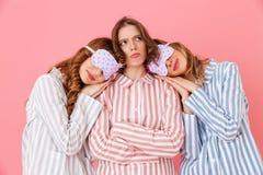 Drie vriendschappelijke jonge meisjesjaren '20 die kleurrijke gestreepte pyjama dragen Royalty-vrije Stock Foto's