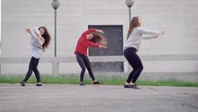 Drie vrij jonge moderne ballerina's is het dansen eigentijdse dansen op een straat, uitvoerend verschillende bewegingen stock video