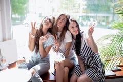 Drie vrij slanke meisjes met lang donker haar, die toevallige stijl dragen, zitten op de vensterbank in een moderne koffiewinkel stock fotografie