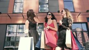 Drie vrij vrouwelijke vrienden die in openlucht en over het winkelen spreken samenkomen stock video