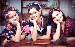 Drie vrolijke huisvrouwen stock afbeelding