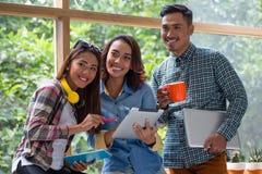 Drie vrolijke jonge werknemers die aan een project samenwerken stock afbeeldingen