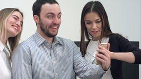 Drie vrolijke medewerkers die grappige selfies op de telefoon nemen stock video