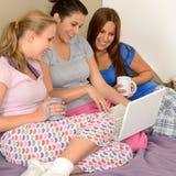 Drie vrolijke meisjes die op het net surfen Royalty-vrije Stock Afbeelding