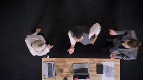 Drie vrolijke multy-etnische arbeiders dansen dichtbij lijst met laptops en glazen met champagne in bureau, bedrijf stock videobeelden