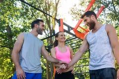 Drie vrolijke vrienden die handen samenbrengen als gebaar van motivatie stock afbeelding