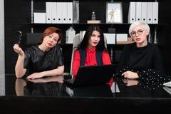 Drie vrouwelijke collega's die in bureau bij lijst met laptop zitten stock afbeelding