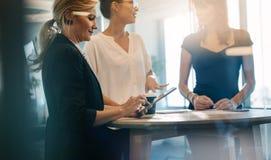 Drie vrouwelijke collega's die een bevindende vergadering hebben stock afbeeldingen