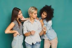 Drie vrouwelijke vrienden die smartphones gebruiken Stock Foto