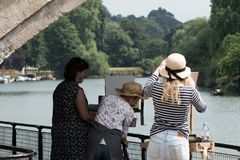Drie vrouwen die een rivierscène schilderen royalty-vrije stock fotografie