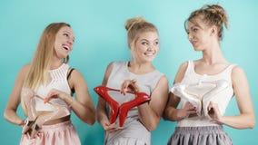 Drie vrouwen die hoge hielenschoenen tonen Stock Fotografie