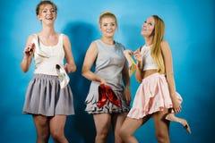 Drie vrouwen die hoge hielenschoenen tonen Stock Foto