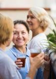 Drie vrouwen die thee drinken bij balkon Stock Afbeeldingen