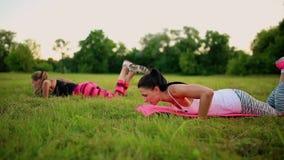 Drie vrouwen doen duw UPS op het gras in het park stock videobeelden