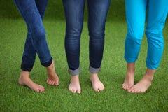 Drie vrouwen met naakte voeten die zich in gras bevinden Royalty-vrije Stock Foto