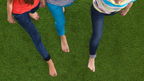 Drie vrouwen met naakte voeten die zich in gras bevinden Royalty-vrije Stock Foto's