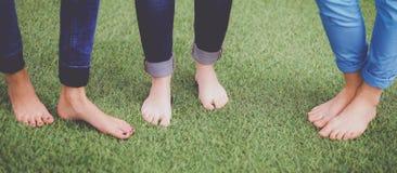 Drie vrouwen met naakte voeten die zich in gras bevinden stock afbeelding