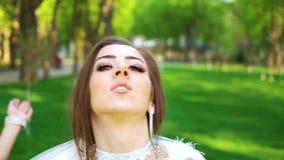 Drie vrouwen in sexy bruid gestileerde kostuumsdans bij dag in zonnig park stock footage