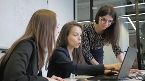 Drie vrouwen werkt, gebruikend laptop en bespreking in modern bureau stock video