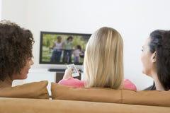 Drie vrouwen in woonkamer het letten op televisie Stock Afbeeldingen