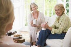 Drie vrouwen in woonkamer met koffie het glimlachen Royalty-vrije Stock Fotografie