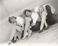 Drie vrouwenzitting op vloer van schip stock foto's