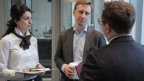 Drie werknemers spreken status in belangrijk bedrijf stock video