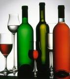 Drie wijnflessen en verscheidene glazen. Stock Fotografie