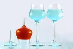 Drie wijnglazen met blauw en oranje water Stock Foto