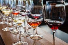 Drie wijnglazen met steekproeven op houten teller Stock Afbeelding