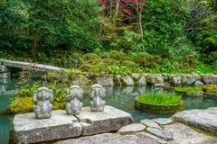DRIE WIJZE APEN Hoor geen kwaad, zie geen kwaad, spreek geen kwaad in een Japanse tuin, Japan Stock Afbeeldingen