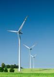 Drie windturbines op groen gebied Stock Fotografie