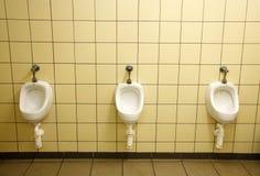 Drie witte ceramische urinoirs op gele muur royalty-vrije stock afbeelding