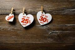 Drie witte harten met kortingen hangen op de wasknijpers op de kabel op bruine houten achtergrond Grote verkoop royalty-vrije stock afbeeldingen