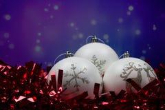 Drie witte Kerstmisballen met sneeuwvlok en rendier voor purpere blauwe achtergrond royalty-vrije stock foto