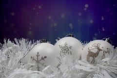 Drie witte Kerstmisballen met sneeuwvlok en rendier voor purpere blauwe achtergrond stock afbeeldingen