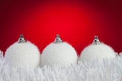 Drie witte Kerstmisballen op klatergoud Stock Foto